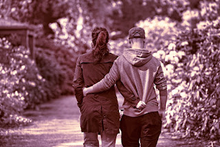 Sepia colored man and woman walking on a forest trail