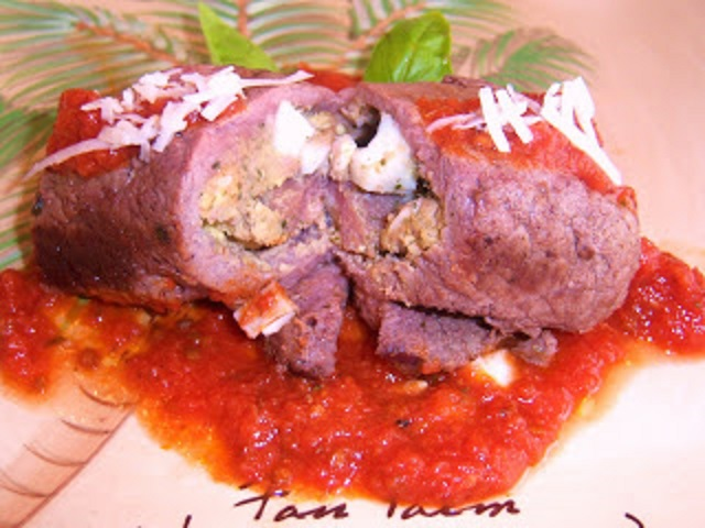 Stuffed meat rolls with boiled egg bread crumbs, cheese and spices in Italian tomato sauce on a plate ready to serve with pasta