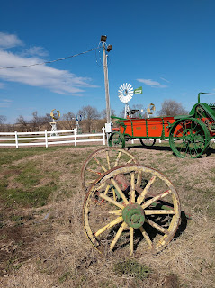 a horse cart and wheels from another cart sit in front of a white fence and an antique windmill in Jackson, Nebraska
