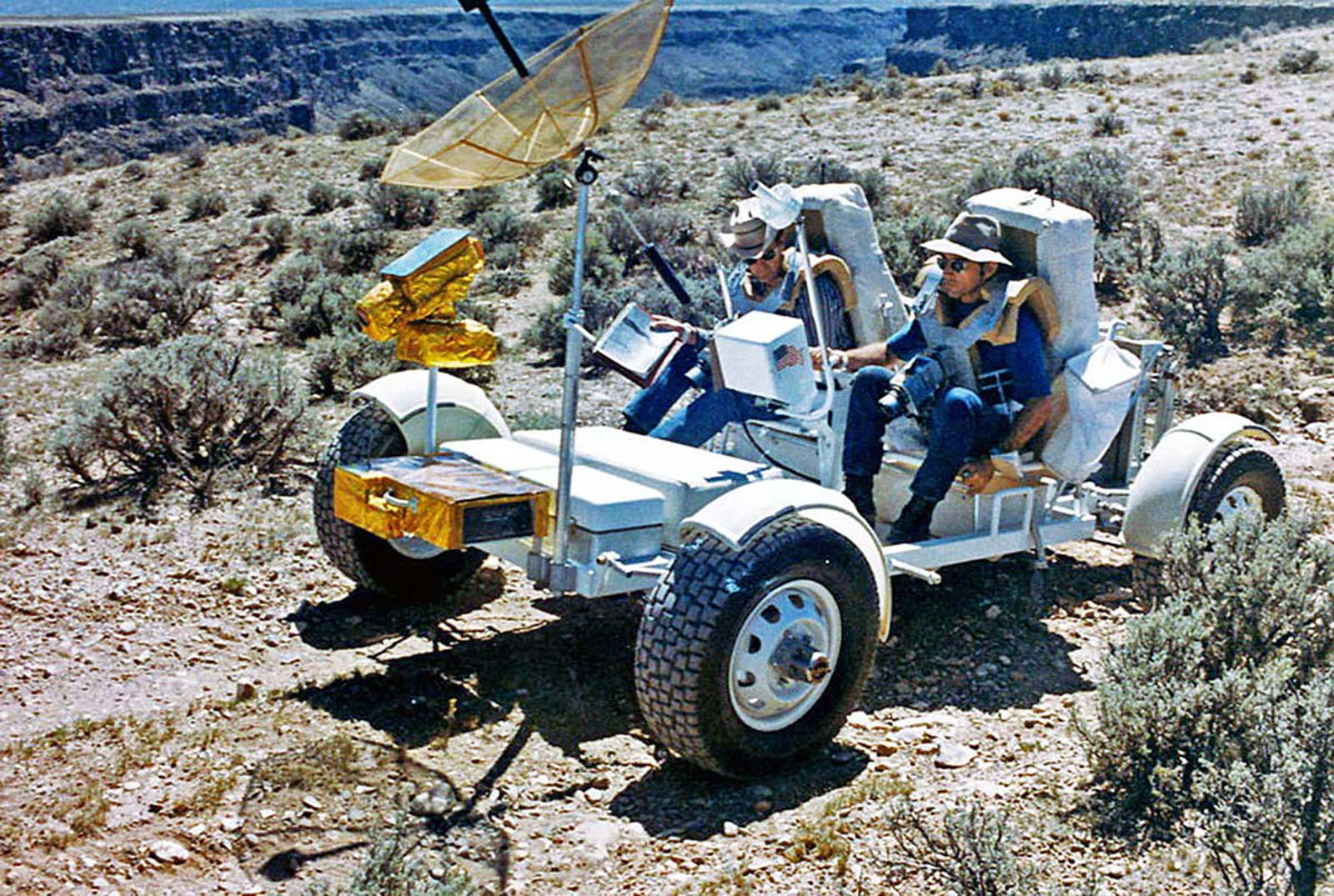 The Apollo astronauts Charles Duke and John Young train on the geological rover, or