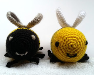 Two crocheted round smiley faces of crocheted bees. Left: black face with silver features and silver wings above.  Right: a yellow round face with black features and white wings above. Underneath and to the sides of the faces are black legs.