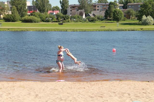Pedeli raskaana uimassa rannalla lapsi