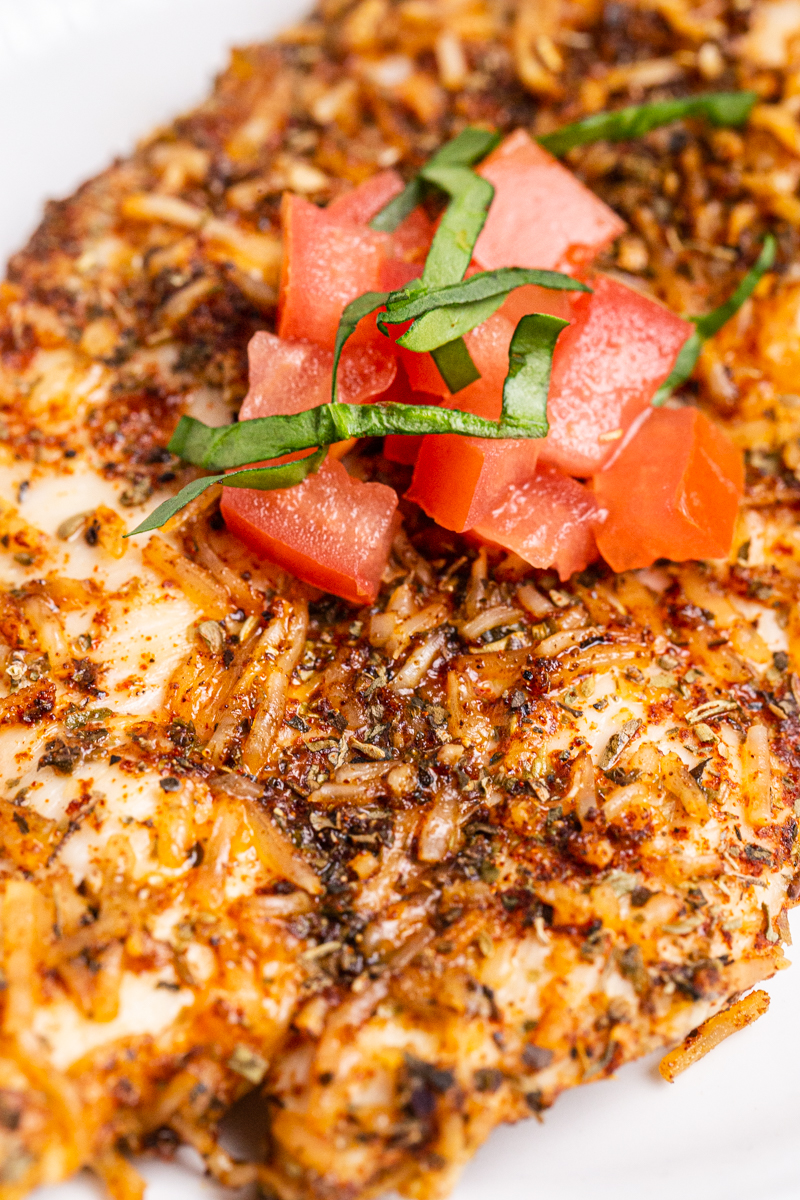 Closeup photo of Keto Parmesan Chicken Cutlets with chopped tomatoes and basil on top.