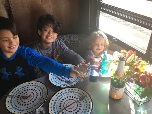 Kids cheers over some sparkling apple cider and Thanksgiving meal