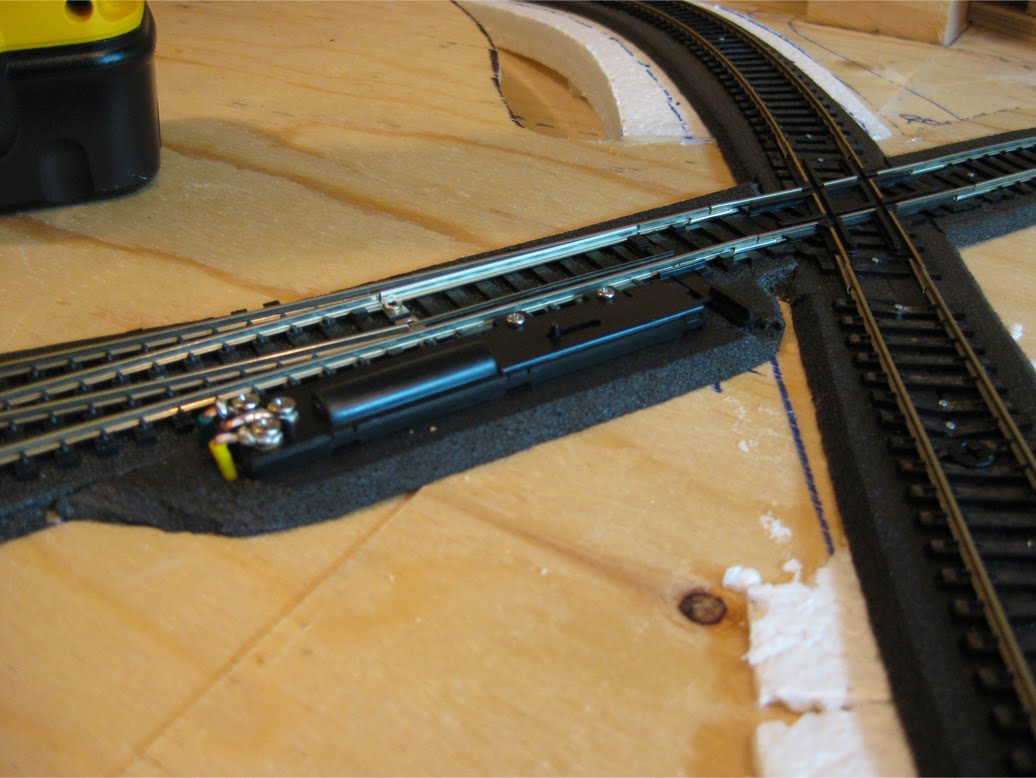 Atlas trackside switch machine installed beside an Atlas turnout on a model railroad layout