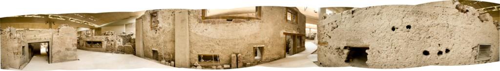 Vista panorámica de 360° de la plaza del Triángulo de Akrotiri. El edificio en el centro es la «Casa del oeste». El edificio de enfrente, que aparece en ambos lados de la imagen, pertenece al sector Delta del complejo.