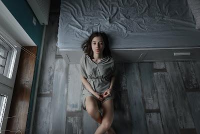Chica con vestido gris y habitación gris sentada en el suelo
