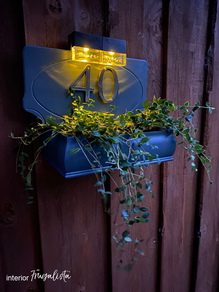 How to build a house number planter box that is backlit at night with solar lights, made from a repurposed Bombay-style jewelry box and wooden plaque.