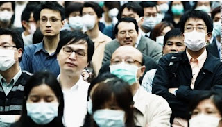 People standing in the street of Wuhan wearing Coronavirus mask