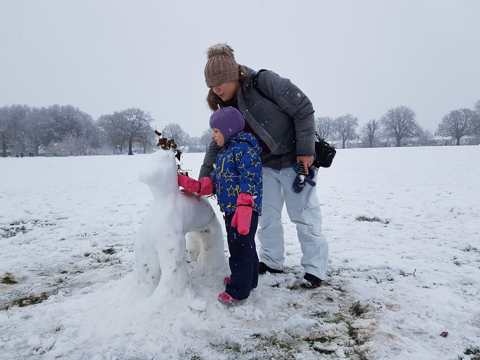 mum and daughter petting the snow pony