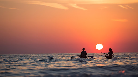 Couple Boat Rowing In Sea During Sunset