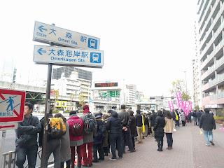 大森海岸駅の標識と沿道にズラリと並ぶ駅伝を応援する人々