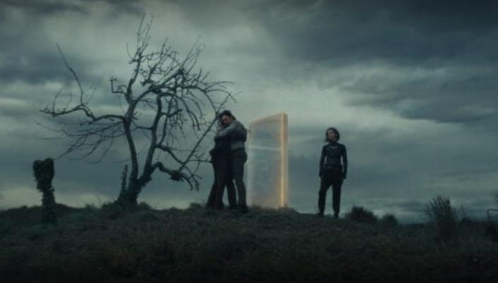 Imagem: Cenário  aberto em um campo com um céu nublado atrás. No centro temos Loki se abraçando com Mobius. Ao lado está Silvye está observando eles e perto deles têm uma porta semi translúcida no ar com brilho dourado em suas bordas.