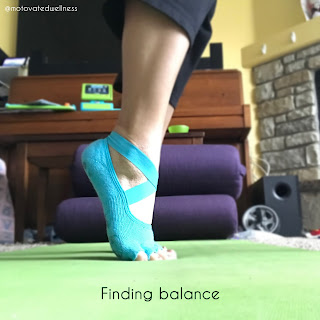 Picture of feet on tip-toe wearing teal yoga socks on a green yoga mat