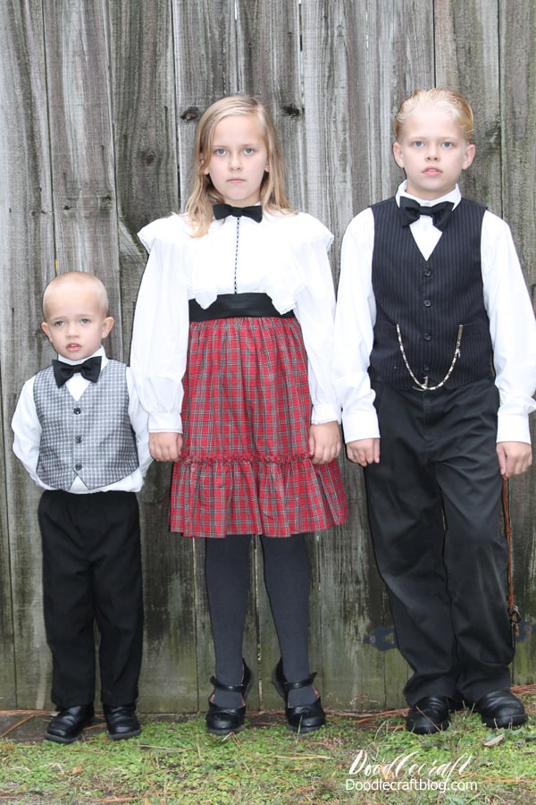 Children dressed like kids from the Victorian age 1800's, with bow ties, pocket watch, sad faces.