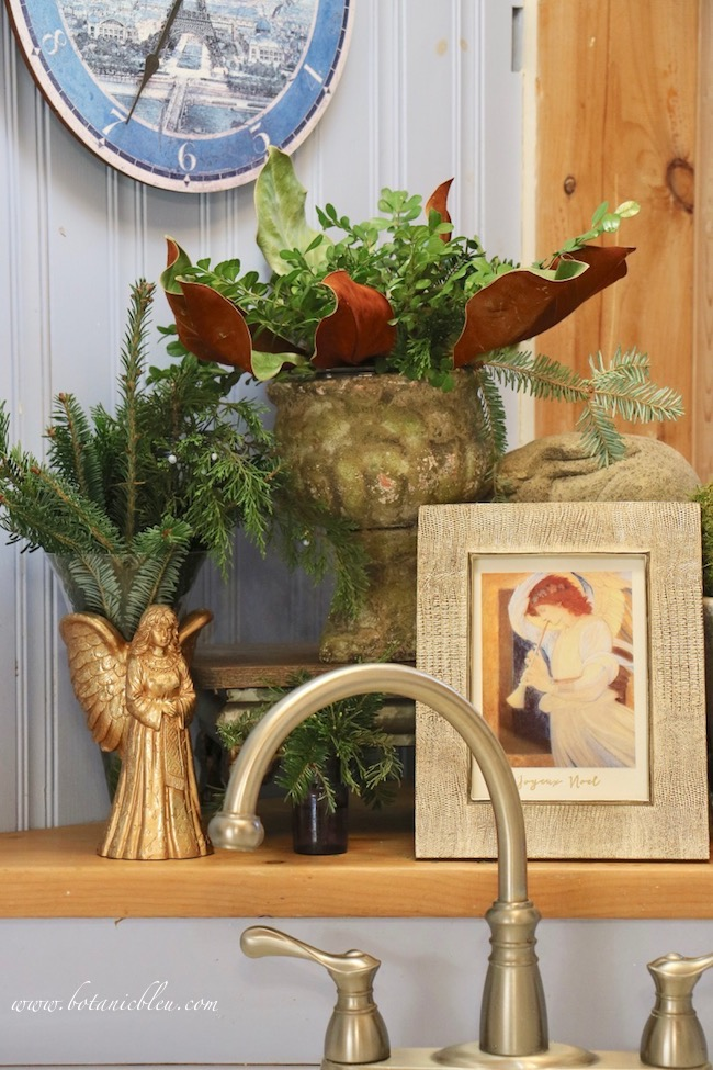 A footed wooden riser elevates a rustic urn filled with magnolia leaves and fresh boxwood above a gold framed angel print