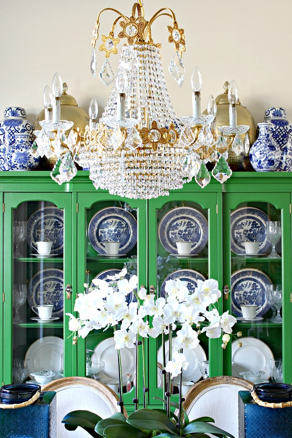 Gorgeous green cabinet with blue and white dishes.