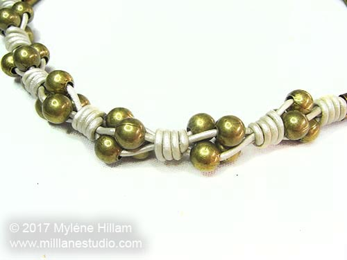 leather cord necklace strung with clusters of brass beads