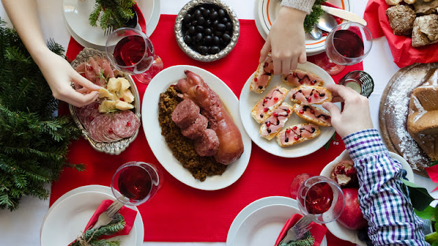 a holiday spread filled with meats, olives, and pastries