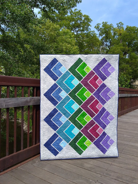 Quilt with bright geometric design on a cream background, on a footbridge