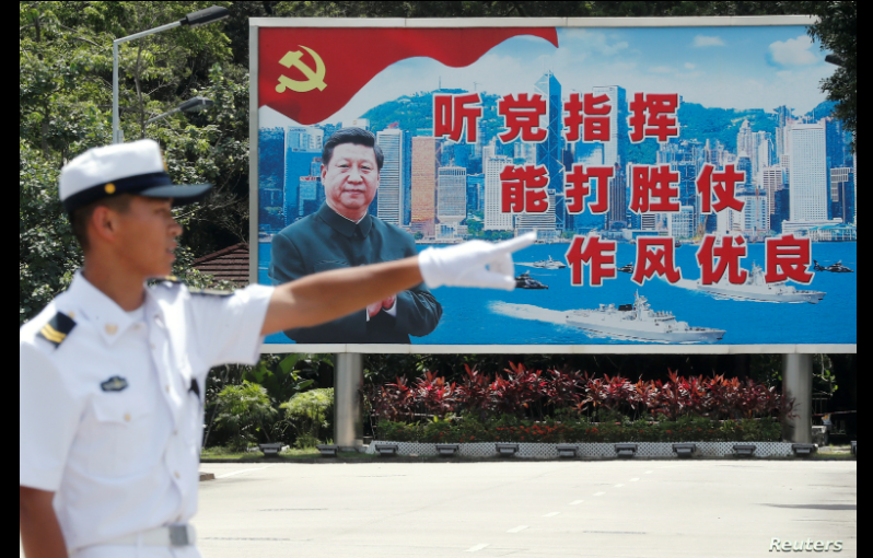 Un soldado naval de China frente a un gran mural del líder Xi Jinping durante una sesión de exhibición en Hong Kong / REUTERS