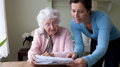 home caregiver assists elderly woman with documents