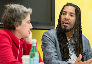 Photo of Kathi Wolfe and L. Lamar Wilson. They sit at a table side by side and Lamar is speaking. Kathi has short gray hair, wears a red sweater and glasses She is listening intently. Lamar has on a grey jacket, a light mustache and well trimmed beard. He is wearing his hair in long locks. There is a yellow wall behind them.
