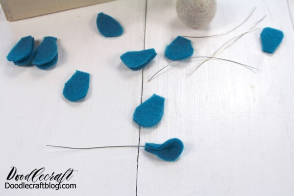 Felt Flower #3: Begin by cutting little tear-drop or petal shapes out of blue felt. Cut the wire about 2 inches long. Then hot glue the wire to the petal and squeeze them together to cover the wire. These make a filler, sort of eucalyptus or little baby breath sprigs.