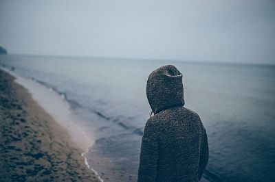 Poema Canciones erróneas en la lejanía. Persona en playa solitaria. Día gris.