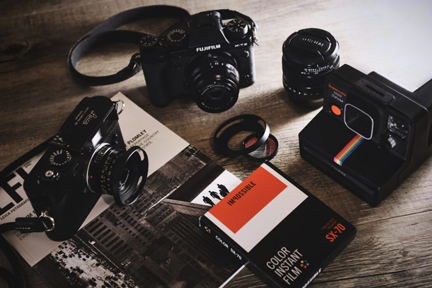 Equipamentos de fotografia sobre uma mesa de madeira; câmeras fotográficas vintage; livro de fotografia