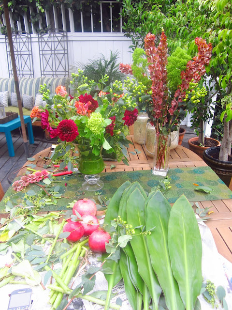 wooden patio table covered in different kinds of flowers and leaves