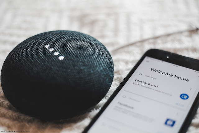 """A black, Google Home Mini lies next to a smart phone. The phone's screen reads: """"Welcome Home"""""""
