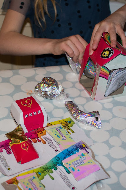 the contents of the drop 3 poop pack include a small cardboard burger box, small fries packet, 2 lots of unicorn food, unicorn magic and a spoon, measuring cup, scent and drink carton in sparkly plastic packaging