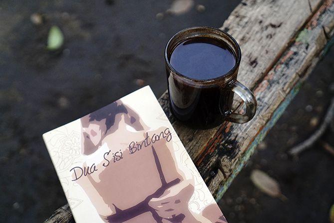 Menyesap kopi dan membaca novel Dua Sisi Bintang