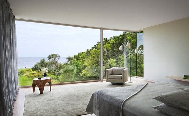 Photo of chair and a coffee table by the window inside of small modern residence on the beach