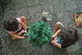 Aerial view looking down on a young boy and girl sitting on the floor preparing to decorate a little Christmas tree