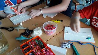 Os alunos t~em à sua volta escamas de todas as cores e passam cola pelos moldes de sardinhas.