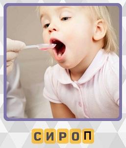 мальчик открыл рот и принимает сироп с ложки в качестве лекарства