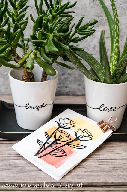 Grünpflanzen in Übertöpfen und Grußkarten