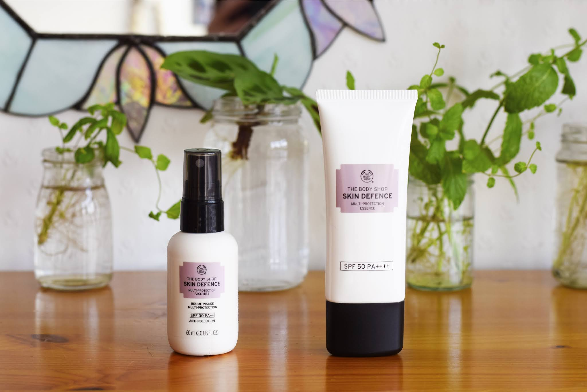 a bottle of skin defence mist and a tube of skin defence moisturiser are placed side by side.