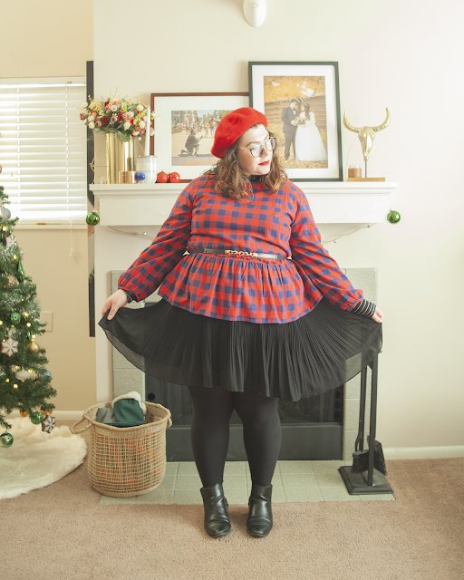 An outfit consisting of a red beret, a black and white turtleneck, a red and blue plaid blouse over a black mini pleated skirt.