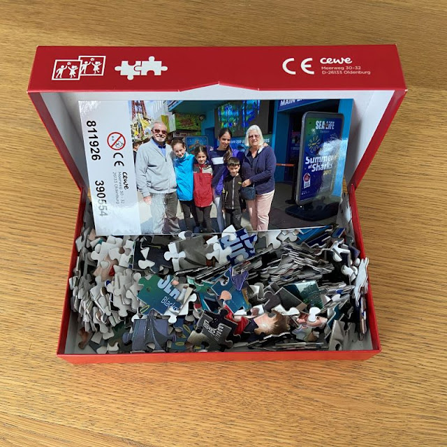 an open box sitting on a table, with lots of jigsaw pieces in it