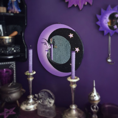 The altar is in the foreground, slightly out of focus; it is on a berry purple altar cloth with a crinkle texture that is on a diagonal to the plane of view. Two silver candle-sticks are upon it, in a classical style, with rolled beeswax purple candles. On the left of the altar is a black plaque displaying a purple pentagram, a small cast iron cauldron with a pentacle on the front, and a partially visible purple glass goblet, cropped out of frame. In the centre is a clear glass candle-holder with a crescent man-in-the-moon and star design moulded into the glass. On the left is an incense censer in the shape of a stylised goddess. Behind the altar and above it is the round crescent moon mirror, it is quite large with a purple crescent moon occupying most of the left of the frame, the right being black with three small stars; the mirrored glass itself is round. The mirror is in focus. To the left of the image the black corner shelving unit is partially visible; the bottom tier has a black stone box with celtic knotwork, a brass Nepalese singing bowl with wooden striker, and partially visible fine-liner print; the print is cropped at the edge of the photograph so the image of the print is not apparent. The second tier is partially visible, with the bottom of the figurine of a wizard in blue, gold and purple robes visible. The shelving unit is slightly out of focus, but the items are identifiable. On the right of the image, a small round moon mirror with a frame consisting of a blueish purple crescent moon and a halo of purple rays is visible, as is a filigree moon pendant with synthetic round stone hanging from it. At the top of the image the halo of rays from the bright purple medium mirror is partially visible. Only the large crescent moon mirror in the centre of the image is in focus, and deliberately so. The photograph is taken in daylight and the shine on metallic objects is quite visible; the black wall is visible in the central mirror, but the wall looks grey in