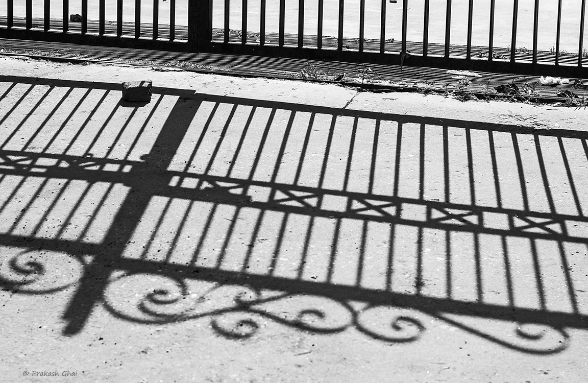 A Black and white Minimalist Photo of Big shadow of a house gate on street.