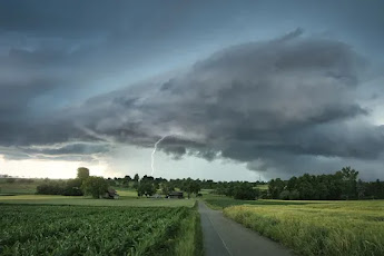 A storm over a green and rural place, with lightning striking the ground.