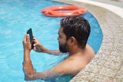 Picture of a man looking at his phone whilst in the pool. Mum (Mom) or Dad: Who is Worse At The Pool?