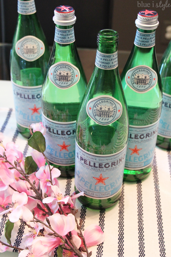 Turn San Pellegrino bottles into vases by adding faux flowers