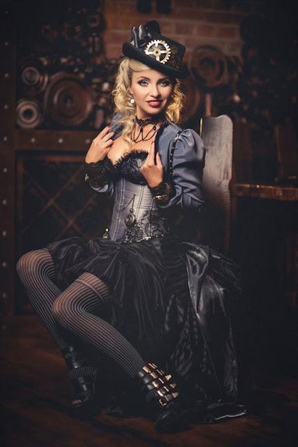 Woman wearing steel blue steampunk dress consisting of corset, bolero jacket, skirt, striped stockings, hat and jewelry
