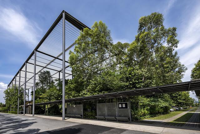 fachada exterior de fábrica con árboles y estructura de acero