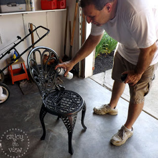 man spray painting a wrought iron chari